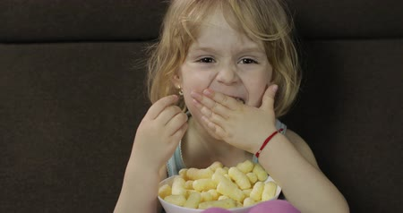 chroupat : Beautiful little blonde girl sitting on a sofa at home and eating corn puffs. Cute child smiling and taste puffcorns. Inside. Childrens meal