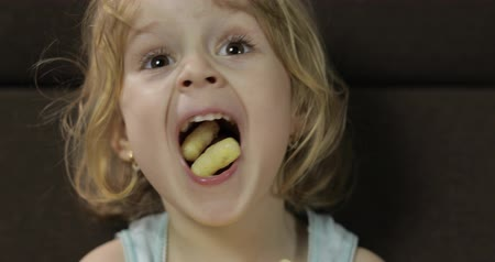chroupat : Beautiful little blonde girl sitting on a sofa at home and eating corn puffs. Cute child smiling and taste puffcorns. Inside. Childrens meal. Close up shot