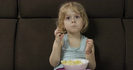 pinda : Beautiful little blonde girl sitting on a sofa at home and eating corn puffs. Cute child watching tv and taste puffcorns. Inside. Childrens meal