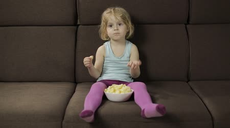 puffs : Beautiful little blonde girl sitting on a sofa at home and eating corn puffs. Cute child watching tv and taste puffcorns. Inside. Childrens meal. Slow motion Stock Footage