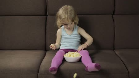 puffs : Beautiful little blonde girl sitting on a sofa at home and eating corn puffs. Cute child smiling and taste puffcorns. Inside. Childrens meal. Slow motion