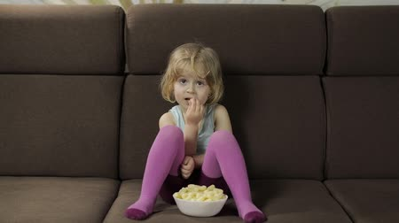 chroupat : Beautiful little blonde girl sitting on a sofa at home and eating corn puffs. Cute child smiling and taste puffcorns. Inside. Childrens meal. Slow motion