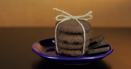 migalhas : Tasty looking chocolate cookie on a blue plate on dark surface. Vintage warm background Stock Footage