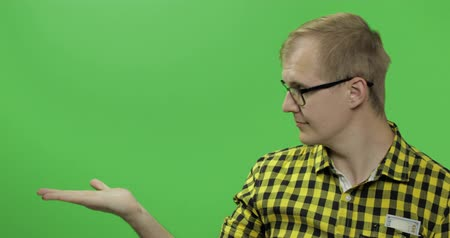 sincerely : Caucasian fashionable man in glasses showing something. Place for your logo or text. Thumbs up. Guy in yellow shirt. Chroma key