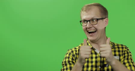 tarkabarka : Caucasian fashionable man in glasses very emotionally showing something. Place for your logo or text. Thumbs up. Guy in yellow shirt. Chroma key