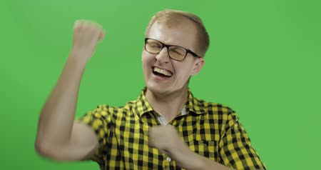 sincerely : Caucasian fashionable man in glasses very emotionally celebrates something. Guy in yellow shirt doing yes gesture with his hand in front of the camera. Chroma key