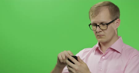 sincerely : Caucasian man in glasses scrolling or texting on the smartphone in his hands. Guy in pink shirt. Place for your logo or text. Green screen. Chroma key Stock Footage