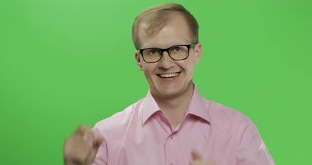 sincerely : Caucasian man in glasses show thumbs up. Guy in pink shirt. Green screen. Chroma key Stock Footage