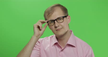 tarkabarka : Handsome young man in the pink shirt and glasses turning his head and looking in the camera on the chroma key background. Green screen. Stock mozgókép