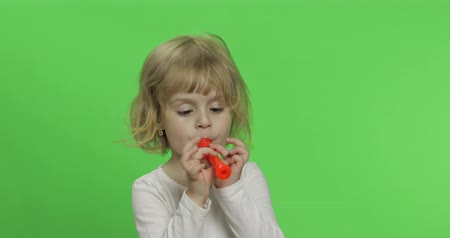fife : Portrait of three years old blonde girl plays on toy pipe on green background. Chroma key