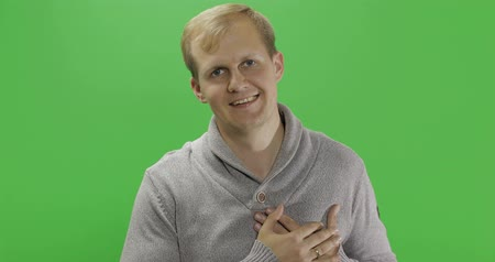 tarkabarka : Handsome young man in the gray sweater doing love gesture over a green screen background. Chroma key