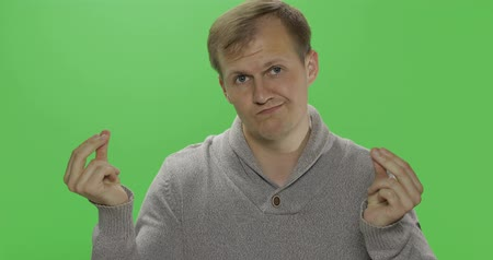 sem camisa : Handsome young man in the gray sweater doing no money gesture over a green screen background. Poverty concept. Chroma key Stock Footage
