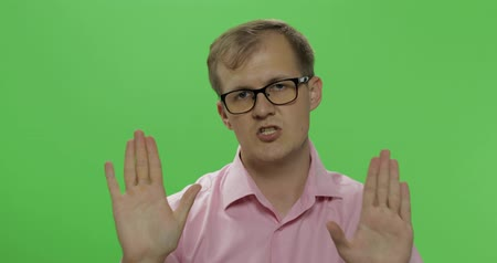 riskantní : Handsome young man in pink shirt saying no and doing stop gesture with a hand over a green screen background. Chroma key