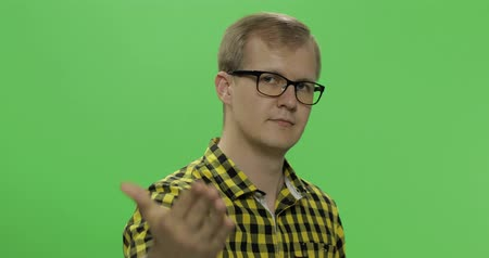 sincerely : Handsome young man in the yellow shirt doing doing coming gesture over a green screen background. Chroma key