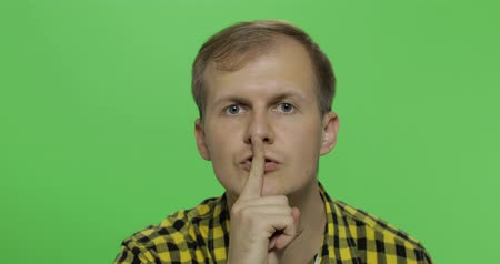 sincerely : Handsome young man in the yellow shirt keeping a secret or asking for silence, serious face, obedience concept on the chroma key background. Green screen Stock Footage
