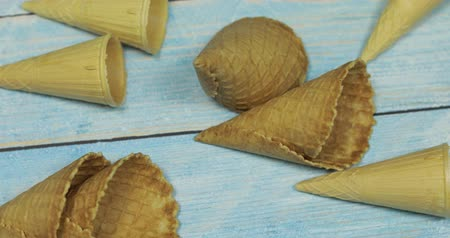 zmrzlinový pohár s ovocem : Ice cream cones, isolated on blue wooden surface. Waffles for ice cream. Dostupné videozáznamy