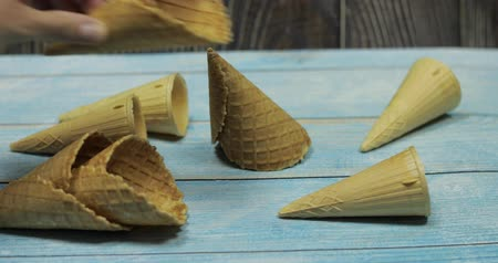 zmrzlinový pohár s ovocem : Ice cream cones, isolated on blue wooden surface. Waffles for ice cream. Mans hand takes one ice cream cone