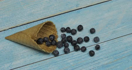 gofret : Berry season. Berry ice cream. Berries of blueberries in a waffle on a blue wooden background Stok Video