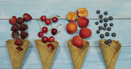 ワッフル : Berry and fruit ice cream. Flat lay various fresh fruits blueberry, strawberry, cherry, apricot in a waffle cone on blue wooden background. Summer sweet menu concept. Homemade ice cream making
