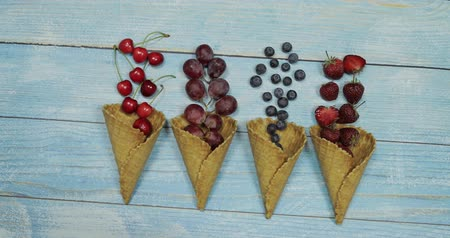 gofret : Berry and fruit ice cream. Flat lay various fresh fruits blueberry, strawberry, cherry, grape in a waffle cone on blue wooden background. Summer sweet menu concept. Homemade ice cream making