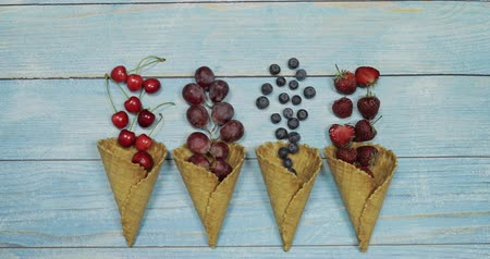 oplatka : Berry and fruit ice cream. Flat lay various fresh fruits blueberry, strawberry, cherry, grape in a waffle cone on blue wooden background. Summer sweet menu concept. Homemade ice cream making
