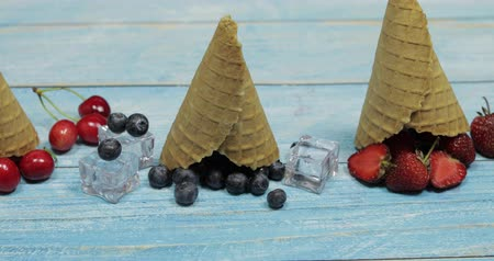 gofret : Berry and fruit ice cream. Flat lay various fresh fruits blueberry, strawberry, cherry in a waffle cone on blue wooden background. Summer sweet menu concept. Homemade ice cream making