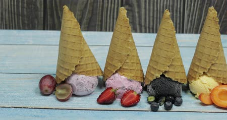 абрикосы : Sweet ice cream in balls on a wooden background. Dessert with different flavors and fresh berries and fruits. Ice cream in a waffle cone. Copy space Стоковые видеозаписи