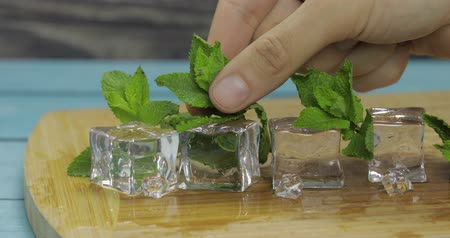 Ice cubes and fresh mint leaves isolated on wooden cutting board. Mans hand takes mint leaves.