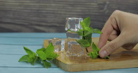 mansão : Ice cubes and fresh mint leaves isolated on wooden cutting board. Mans hand takes mint leaves for mojito cocktail