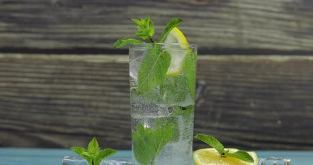 tonik : Clear water in glass with green mint leaves and ice cubes on wooden background. Woman puts mint leaves on the top of the drinking glass.