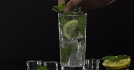 tonik : Clear water in glass with green mint leaves and ice cubes on black background. Puts mint leaves on the top of the drinking glass. Stok Video