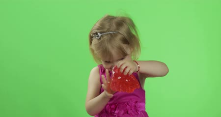 trecho : Child having fun making red slime. Kid playing with hand made toy slime. Funny kid girl. Relax and Satisfaction. Oddly satisfying blue slime for pure fun and stress relief. Green screen. Chroma Key