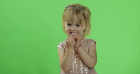 duygusallık : Girl in glossy dress begins to eat chewing gum candy. Happy four years old girl. Pretty little child, 3-4 year old blonde girl. Make faces. Bubble gum. Green screen. Chroma Key
