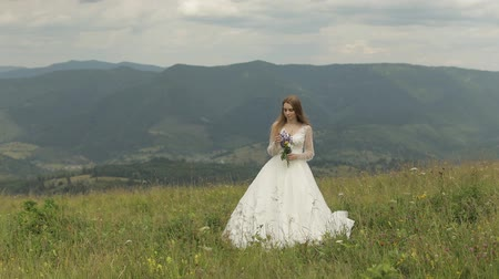 preparált : Beautiful and lovely bride in wedding dress stay on the mountains with bouquet of flowers. Pretty and well-groomed woman. Wedding day. Slow motion