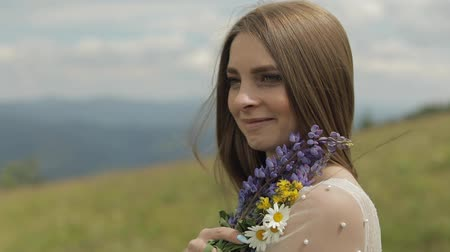 oczy : Close up shot of brides face. Beautiful and lovely bride in wedding dress stay on the mountains with bouquet of flowers. Pretty and well-groomed woman. Wedding day. Slow motion Wideo