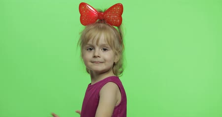 duygusallık : Girl in purple dress and red ribbon on head dancing. Happy four years old girl. Pretty little child, 3-4 year old blonde girl. Make faces and smile. Green screen. Chroma Key