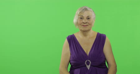 érettség : An elderly woman waving to camera and smiles. Old pretty grandmother in a purple dress. Place for your logo or text. Chroma key. Green screen background
