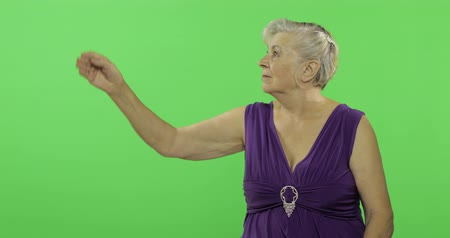 gesticulation : An elderly woman points at something and smiles. Old pretty grandmother in a purple dress. Place for your logo or text. Chroma key. Green screen background