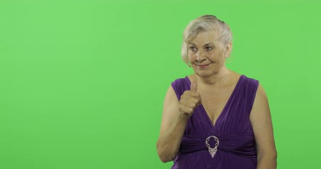 szare tło : An elderly woman points at something and smiles. Old pretty grandmother in a purple dress. Place for your logo or text. Chroma key. Green screen background