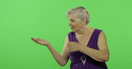 madurez : An elderly woman points at something presenting with open hand palm and smiles. Old pretty grandmother in a purple dress. Place for your logo or text. Chroma key. Green screen background Archivo de Video