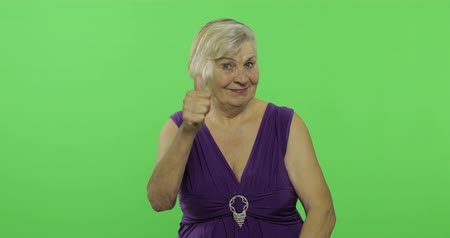 gesticulation : An elderly woman show thumb up and smiles. Old pretty grandmother in a purple dress. Place for your logo or text. Chroma key. Green screen background Stock Footage
