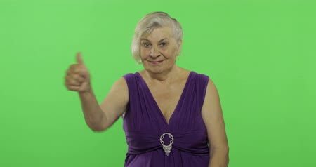 érettség : An elderly woman show thumb up and smiles. Old pretty grandmother in a purple dress. Place for your logo or text. Chroma key. Green screen background Stock mozgókép