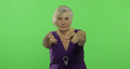 madurez : An elderly woman points at the camera and smiles. Old pretty grandmother in a purple dress. Place for your logo or text. Chroma key. Green screen background Archivo de Video