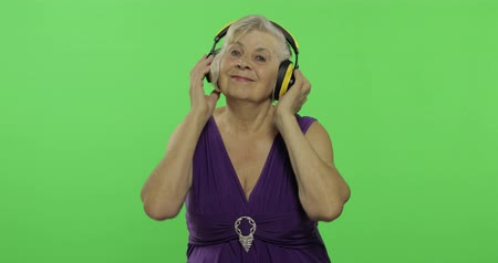 érettség : An elderly woman listens to music in headphones and dances. Old pretty grandmother in a purple dress. Place for your logo or text. Chroma key. Green screen background