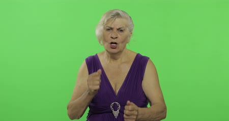 scold : An elderly woman quarrels at someone. Old unkind grandmother scolding in a purple dress. Place for your logo or text. Chroma key. Green screen background