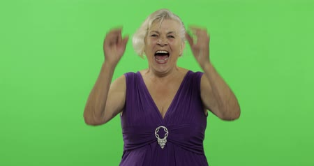 gesticulation : An elderly woman laughing. Old pretty happy grandmother in a purple dress. Place for your logo or text. Chroma key. Green screen background