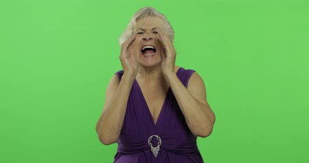 érettség : An elderly woman shout. Old pretty grandmother in a purple dress. Place for your logo or text. Chroma key. Green screen background