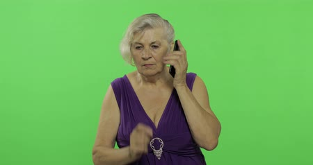 gesticulation : An elderly woman talks on a smartphone. Old pretty grandmother in a purple dress. Place for your logo or text. Chroma key. Green screen background