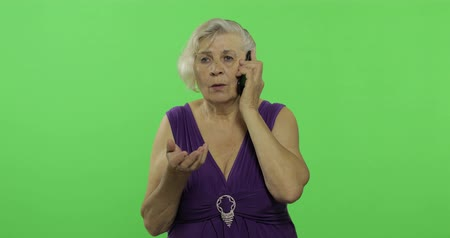 érettség : An elderly woman talks on a smartphone. Old pretty grandmother in a purple dress. Place for your logo or text. Chroma key. Green screen background
