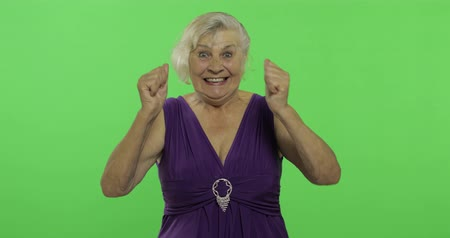 érettség : An elderly woman shows amazement, joy and smiles. Old pretty happy grandmother in a purple dress. Place for your logo or text. Chroma key. Green screen background